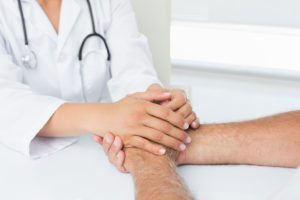 Doctor holding man's hands
