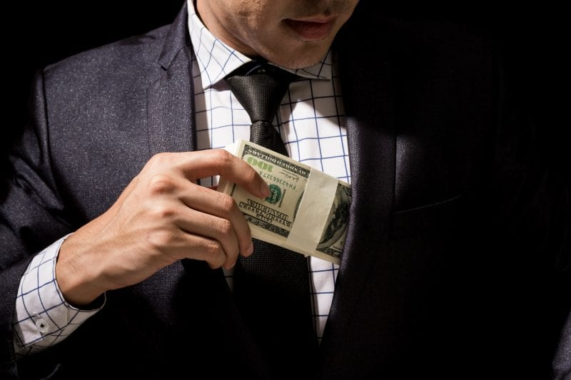 Man putting money in suit pocket